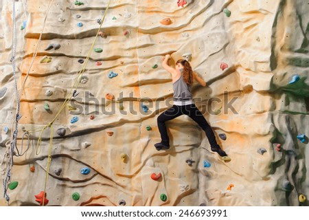 Woman climbing on man-made cliff in the sport centre - stock photo