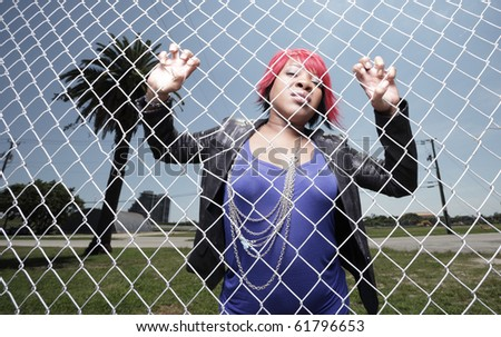 Woman climbing the fence - stock photo