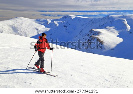Woman climbing the mountain on touring skis in sunny winter day - stock photo