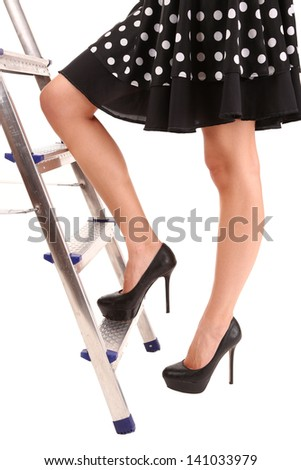 Woman climbing up ladder isolated on white - stock photo