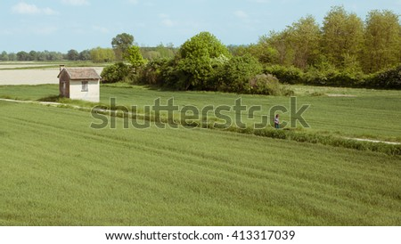 woman climbs a hill with her dog on a walk in a green field