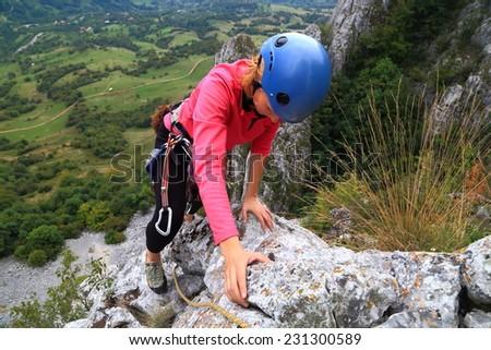 Woman climbs on exposed rock ridge  - stock photo