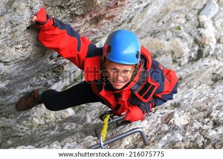 "Woman climbs on narrow gap between rock walls on via ferrata ""Meisules"", Sella massif, Dolomite Alps, Italy - stock photo"