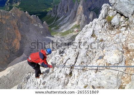 Woman climbs on via ferrata route high above ground, Cadini di Misurina, Dolomite Alps, Italy - stock photo