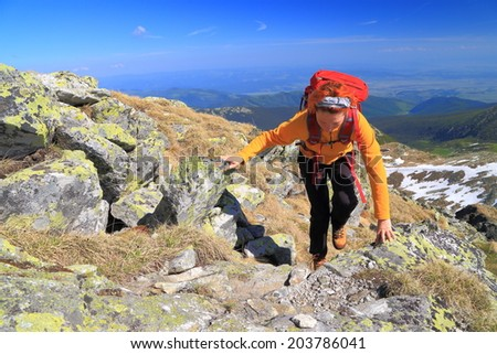 Woman climbs steep trail on the mountains in sunny day - stock photo