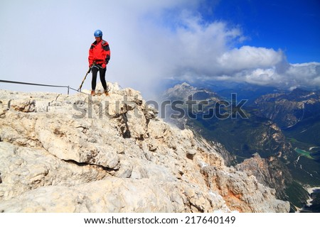 "Woman climbs via ferrata ""Marino Bianchi"", Cristallo massif, Dolomite Alps, Italy"