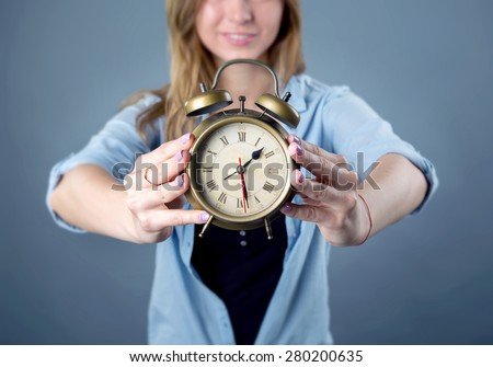 Woman, clock and time. Woman holds before itself in the hands of the clock. Only hands clock close-up on a blue background. European woman with an alarm clock in his hands. Girl shows at the clock.