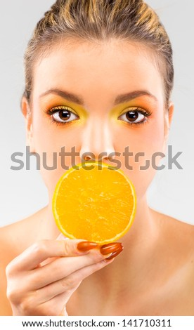 Woman close up with a orange slice - stock photo