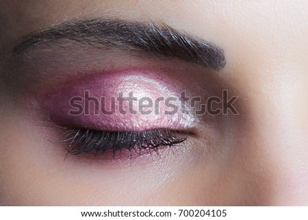 woman closed eye with perfect pink  wet eyeshadow closeup studio