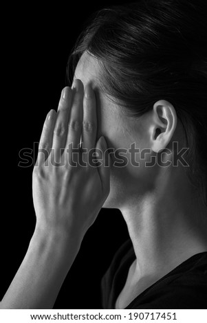 Woman closes her face by hand, tired woman, monochrome image