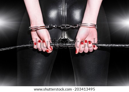 Woman closeup in latex catsuit, whip and handcuffs, bdsm - stock photo