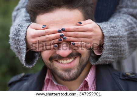 Woman closing his man's eyes for guessing on the street. Handsome man dreaming about real surprise. - stock photo