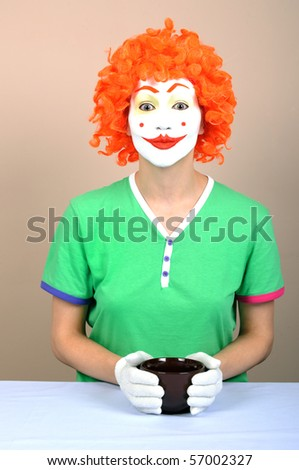 Woman clown with cup in studio. - stock photo
