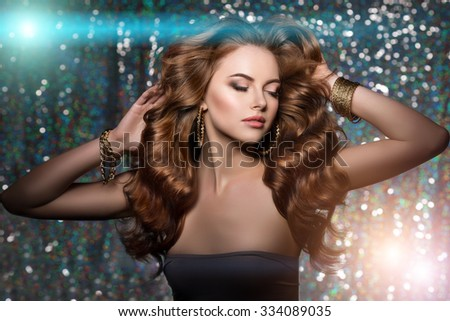 Woman club lights party background. Dancing girl Long hair. Waves Curls Updo Hairstyle Hair Salon. Fashion model shiny hair. Woman healthy hair luxurious haircut Hair volume Jewelry Bracelets Earrings