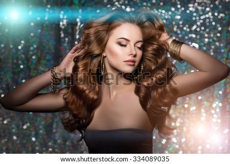 Woman club lights party background. Dancing girl Long hair. Waves Curls Updo Hairstyle Hair Salon. Fashion model shiny hair. Woman healthy hair luxurious haircut Hair volume Jewelry Bracelets Earrings - stock photo