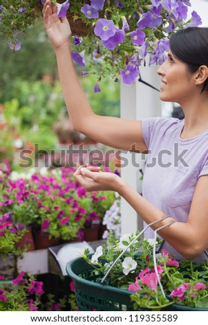 Woman collecting flowers in garden center and putting them in her basket