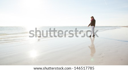 Woman Collecting Shells on a Cold Day at the Beach - stock photo