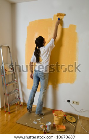 Woman colours her first flat - stock photo