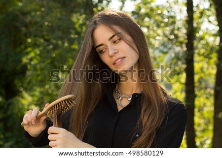 Woman combing her hair in the park