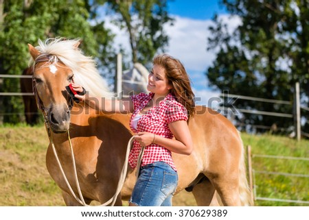 Woman combing pony on horse stable - stock photo