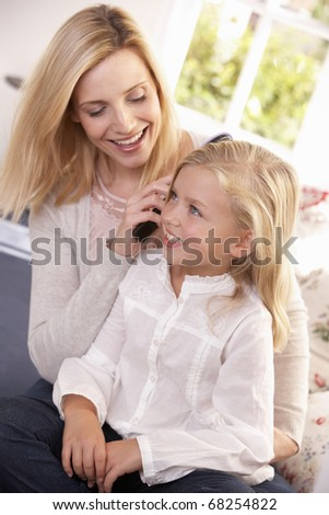 Woman combs hair of young girl - stock photo