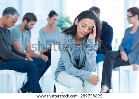 Woman comforting another in rehab group at a therapy session - stock photo