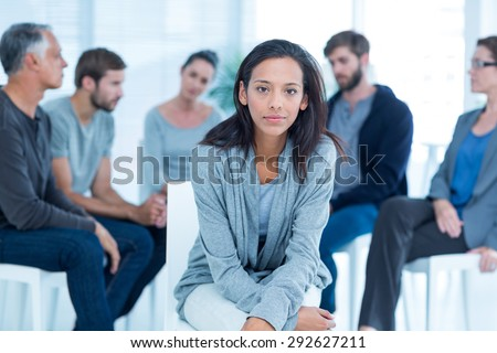 Woman comforting another in rehab group at a therapy session
