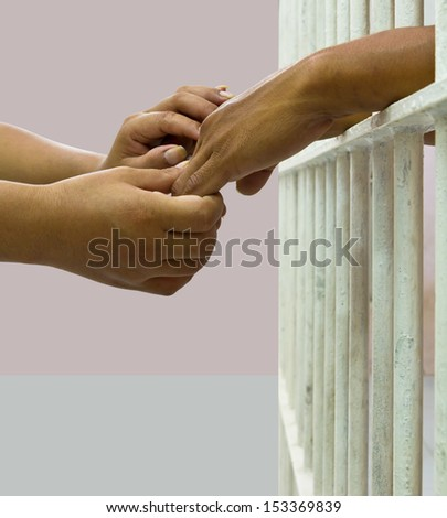Woman comforting man in prison by holding his hand gently  - stock photo
