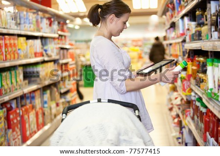 Woman comparing products with a tablet comptuer in a supermarket - stock photo