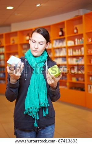 Woman comparing two different products in a pharmacy - stock photo