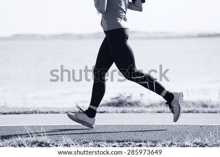 Woman compete in the marathon race on coastal road - stock photo