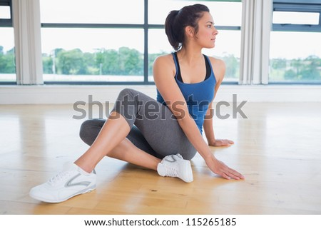Woman concentrating on yoga pose in fitness studio - stock photo