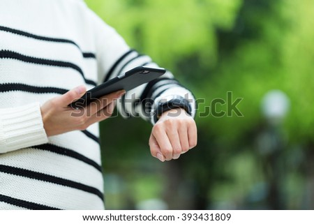 Woman connecting mobile phone with smart watch
