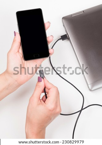 Woman connecting smartphone to a notebook to charge the battery - stock photo