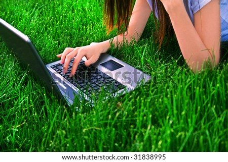 woman connecting the internet with her laptop at the park (above view) - stock photo