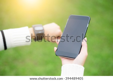 Woman connecting watch and cellphone