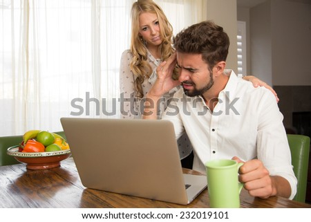 Woman consoling her husband after reading bad news - stock photo