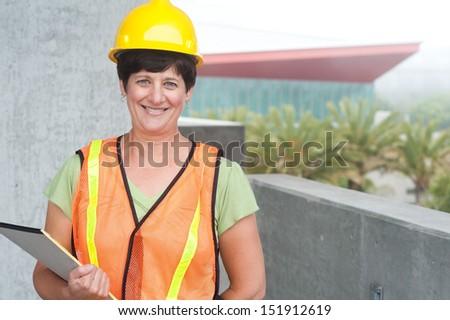 Woman construction worker in hard hat taken outside - stock photo