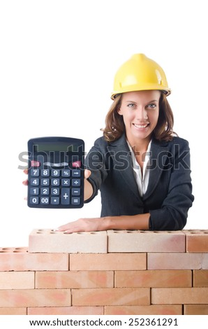Woman construction worker with calculator on white - stock photo