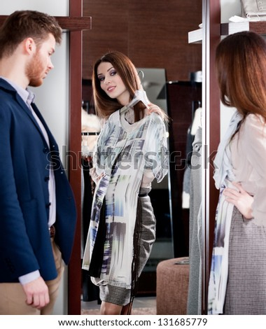 Woman consults with boyfriend while trying on a dress