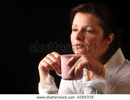 Woman contemplating life over a cup of coffee - stock photo