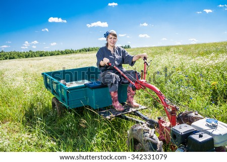 woman controls the tiller with trolley - stock photo