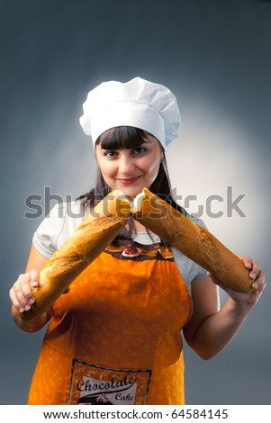 woman cook breaking a french bread - stock photo