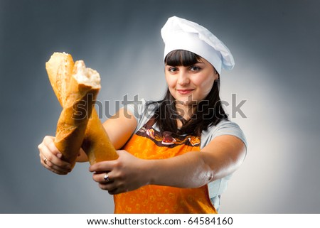 woman cook crossing a french bread - stock photo