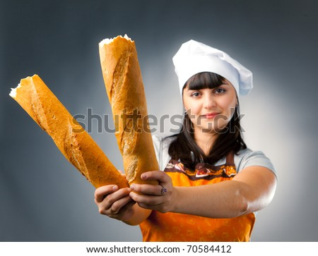 woman cook holding broken  french bread, focus on the bread - stock photo