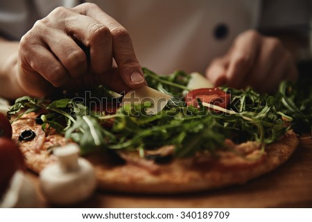 Woman cook pizza with arugula, parmesan and vegetables on wood table in the kitchen.  - stock photo