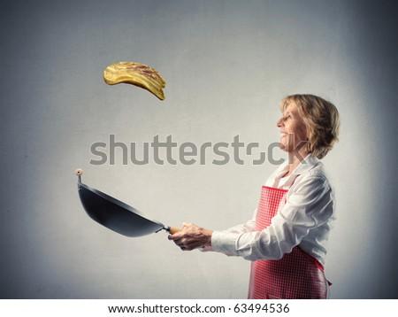 Woman cooking a pancake - stock photo