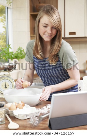 Woman Cooking And Following Recipe On Digital Tablet - stock photo