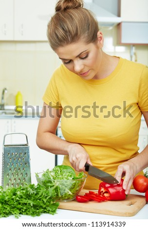 woman cooking  healthy food in the kitchen with knife - stock photo