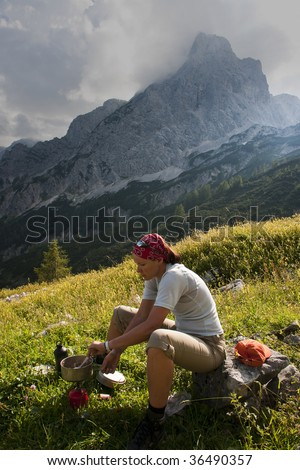 woman cooking in the mountains - stock photo